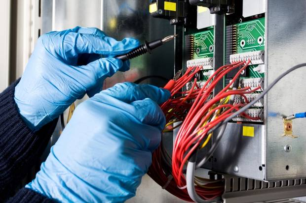 специалист, ремонтирующий шкаф управления подъемника
